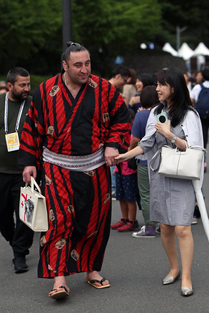 Он же недалеко от стадиона. В окружении болельщиков. Сумоисты в Японии невероятно популярны.